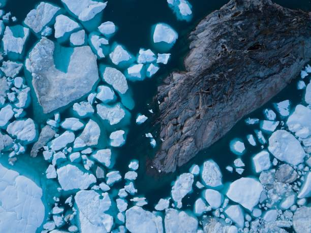 Icebergs drone aerial image top view - Climate Change and Global Warming. Icebergs from melting glacier in icefjord in Ilulissat, Greenland. Arctic nature ice landscape in Unesco World Heritage Site. Background nature concept glacier stock pictures, royalty-free photos & images
