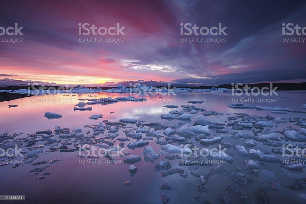 Icebergs floating in Fjallsarlon glacier lake at sunset stock photo