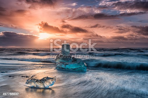 Icebergs floating on Icy beach. Sunrise. South Iceland.