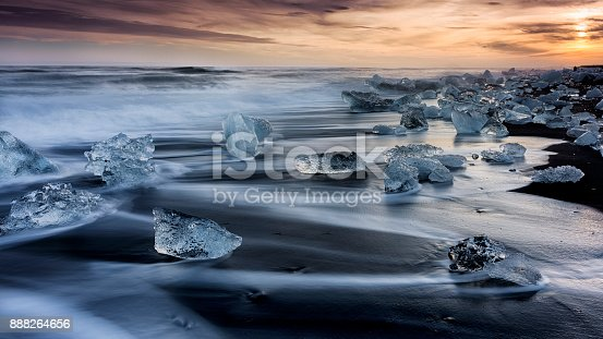Icebergs on icy beach forming interesting lines and shapes between black volcanic lava and spraying seawater, sunset