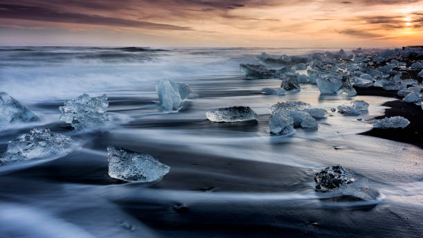 Icebergs on Icy Beach at Sunset, South Iceland, Jokulsarlon Lagoon Icebergs on icy beach forming interesting lines and shapes between black volcanic lava and spraying seawater, sunset jokulsarlon stock pictures, royalty-free photos & images