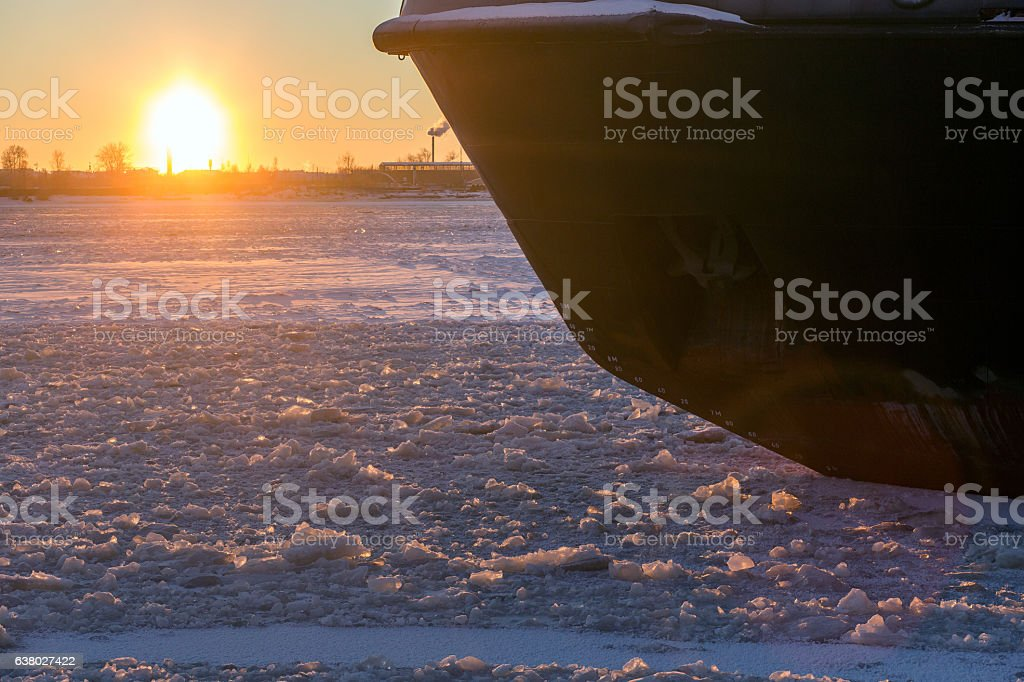 Icebreaker in the river ice on winter sunset. Nose of stock photo
