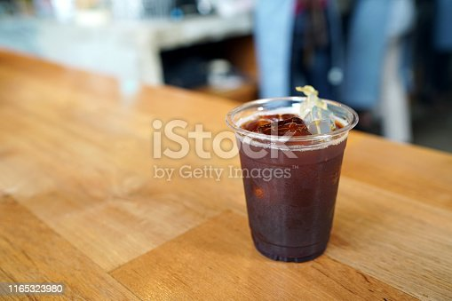 Iced Americano - A plastic glass of black coffee on table and copy space, The style of coffee prepared by brewing espresso and mixed with water, Perfect for breakfast time, Refreshing summer drink concept.
