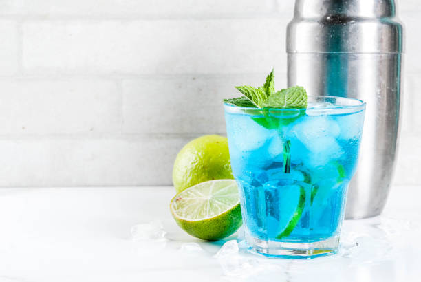 Iced blue alcohol cocktail Colorful summer beverage, iced blue lagoon alcohol cocktail drink with lime and mint, white marble background copy space white marble stock pictures, royalty-free photos & images