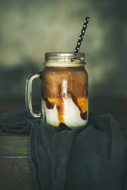 iced caramel macciato milchkaffee im glas - hausgemachter eiskaffee stock-fotos und bilder