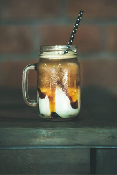 iced caramel macciato milchkaffee im glas, seitenansicht - hausgemachter eiskaffee stock-fotos und bilder