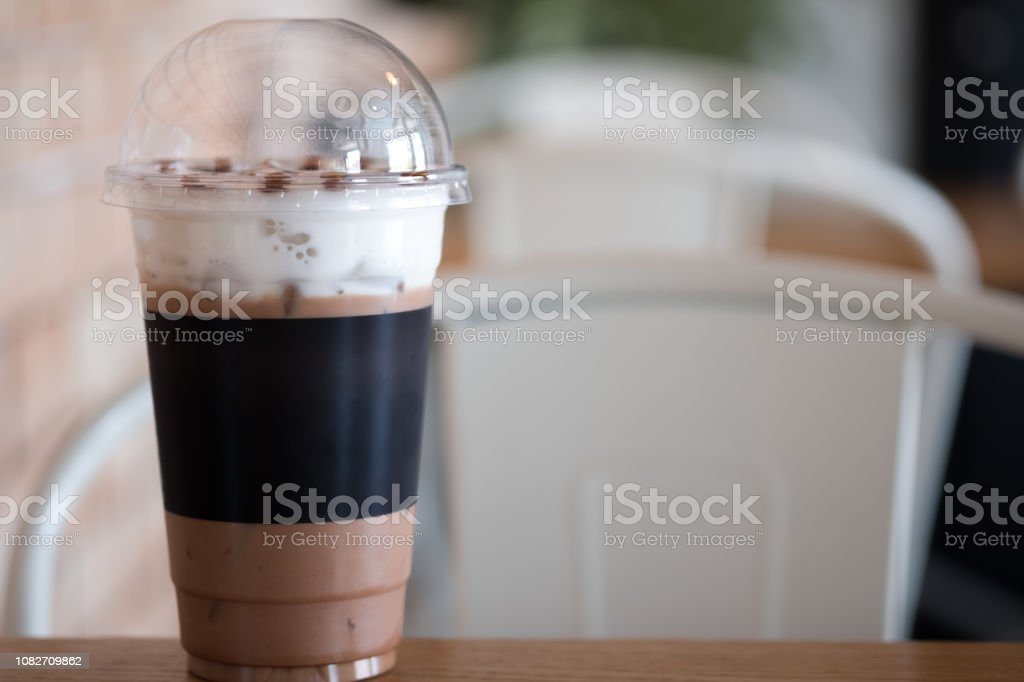 Iced chocolate cocoa glass and straw on table in coffee shop stock photo