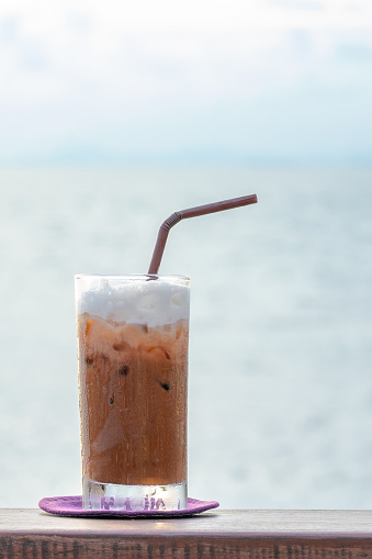 Iced chocolate in a glass on wooden table with sea background
