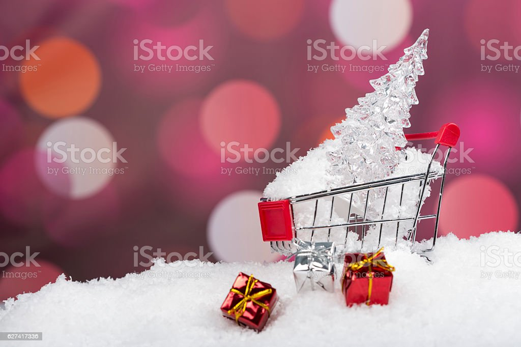 Iced Christmas Tree in shoping cart with gift boxes stock photo
