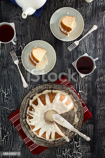Top down image of two slices cut from an iced cinnamon bundt cake and placed on matching plates next to two cups of tea. The rest of the cake is on a metal tray and there is a teapot in the corner of the vintage crackled paint table.