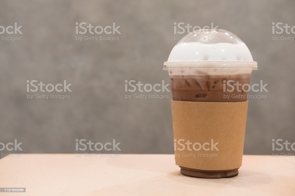 Iced cocoa in takeaway cup on table in coffee shop