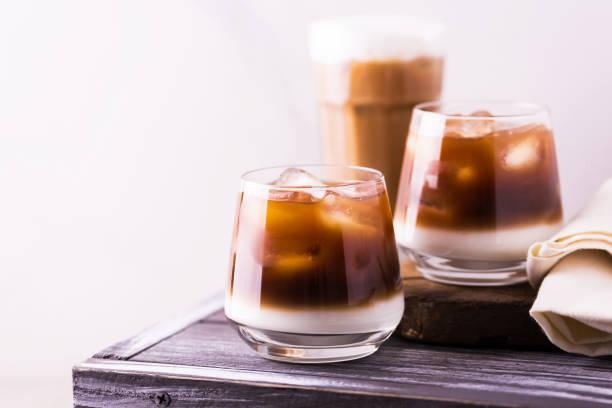 eiskaffee im glas mit milch. schwarzem hintergrund - mocca stock-fotos und bilder