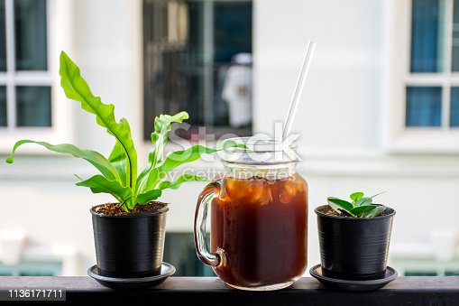 istock Iced coffee near small tree with blurred background. 1136171711
