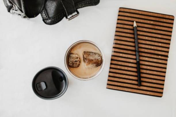 eiskaffee zu gehen. gefroren kaffee eiswürfel in einer thermoskanne mit milch gegossen. wohnung lag der frau handtasche und notiz-buch mit bleistift. weißer hintergrund, isoliert, raum zu kopieren. - hausgemachter eiskaffee stock-fotos und bilder