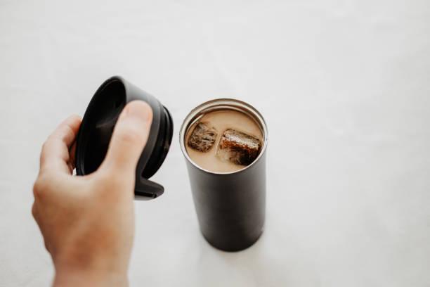 eiskaffee zu gehen. gefroren kaffee eiswürfel in einer thermoskanne mit milch gegossen. hand, einen thermoskanne deckel über der flasche. weißer hintergrund, körperteile, persönlichen gesichtspunkt erschossen. kopieren sie isoliert, raum. - hausgemachter eiskaffee stock-fotos und bilder