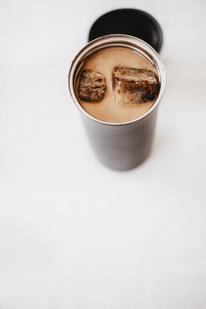 eiskaffee zu gehen. gefroren kaffee eiswürfel in einer thermoskanne mit milch gegossen. thermoskanne deckel in der nähe von der flasche. weißen hintergrund. kopieren sie isoliert, raum. - hausgemachter eiskaffee stock-fotos und bilder