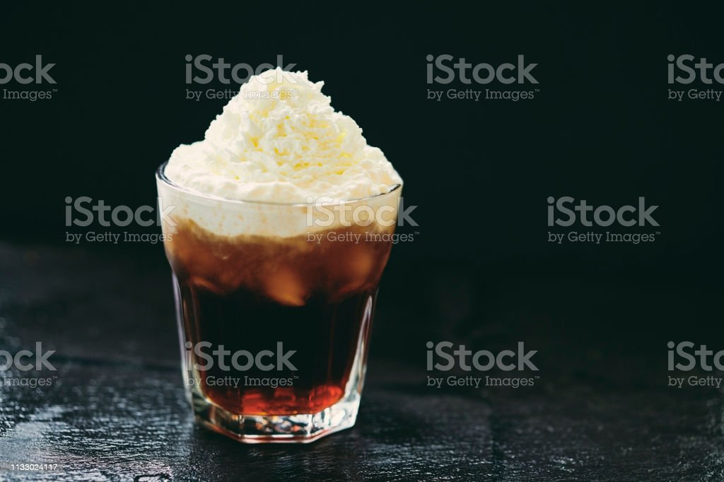 Iced coffee topped with whipped cream. stock photo