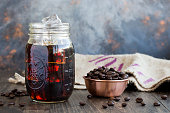 Iced coffee in a glass jar with coffee beans in a copper bowl.