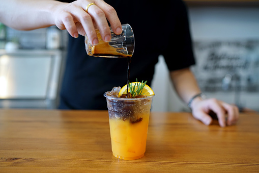 istock Iced coffee with orange - A plastic glass of espresso shot mixed with orange juice and craft soda. 1170254203