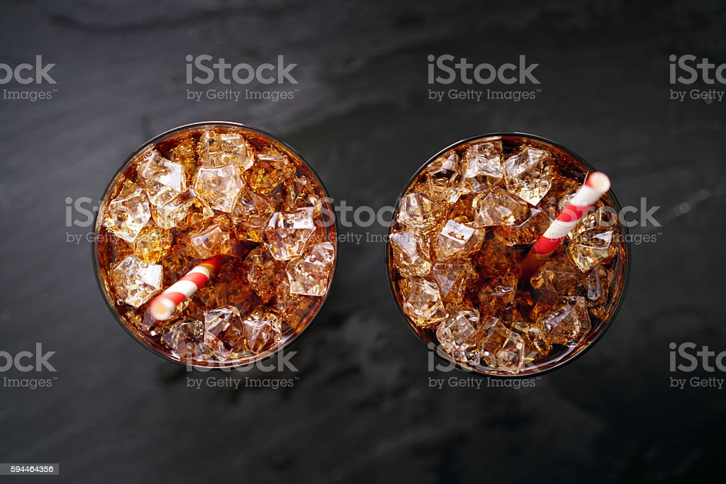 iced cola soda pop with straw in flay lay composition
