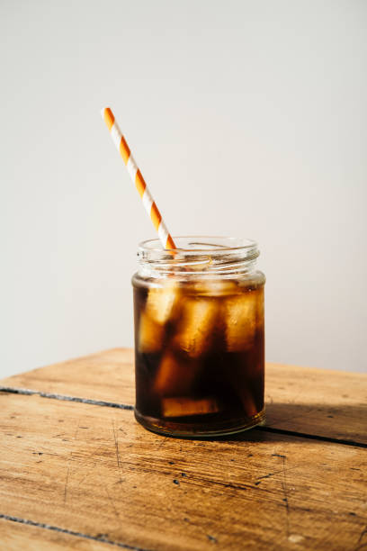 iced cold brew coffee in masonry jar with straw. - iced coffee stock pictures, royalty-free photos & images