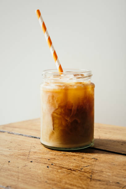 iced cold brew coffee with milk served in a masonry jar. - iced coffee stock pictures, royalty-free photos & images