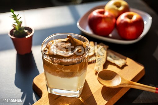 Delicious homemade Iced Dalgona Coffee, a trendy fluffy creamy served on a table, with a plate of apple as background