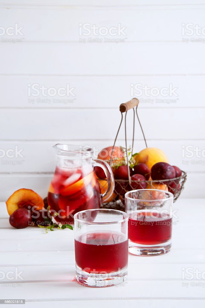 Iced fruit compote with peaches and plums. Cold summer drink. stock photo