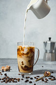 Iced latte coffee in cup glass with pouring milk on grey