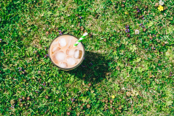 iced latte coffee outdoors in the garden on a sunny day. - iced coffee stock pictures, royalty-free photos & images