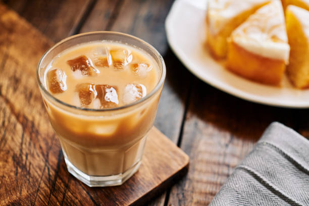 iced latte coffee with lemon drizzle cake on a dark wooden rustic tabletop. - cake stock pictures, royalty-free photos & images