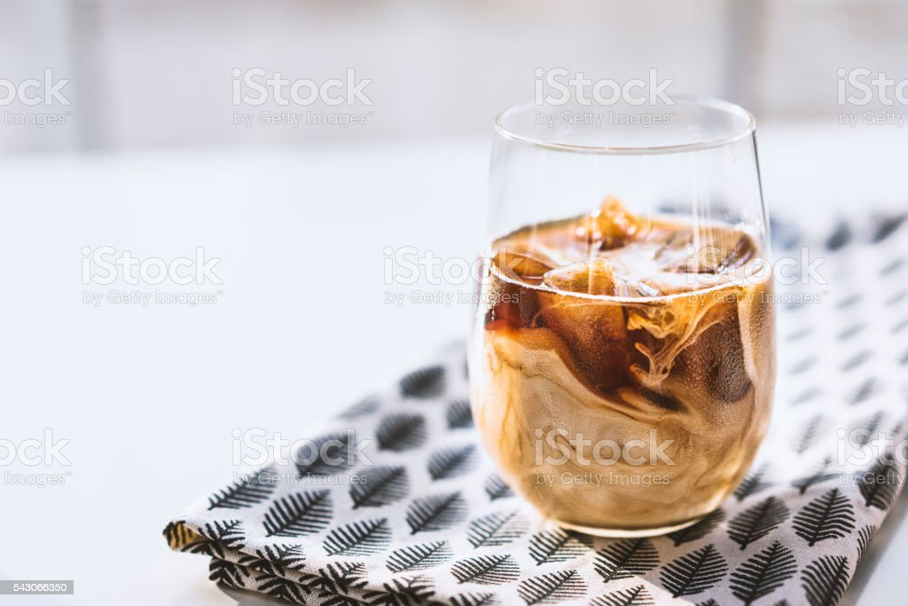 Iced latte on leaf patterned tea towel stock photo