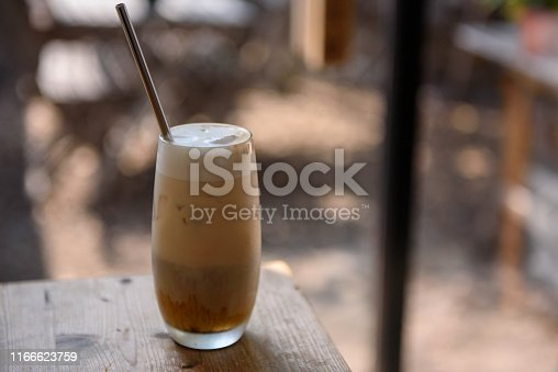 Iced latte with stainless steel straw on wooden table