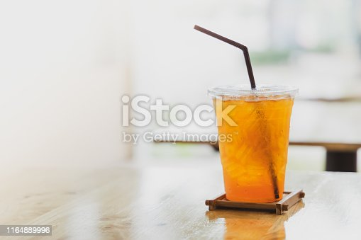 Iced lemon tea in plastic cup with brown plastic straw with blured cafe background.