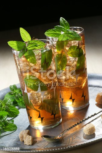 Two tall glasses of iced Morrocan mint tea with brown sugar and fresh mint.