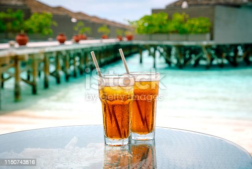 Iced tea against tropical Overwater Bungalow Resort on the beach. Maldives.