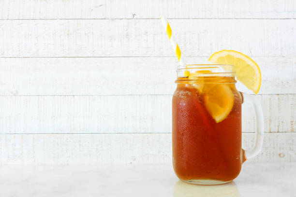 Iced tea in a mason jar glass, side view against white wood stock photo