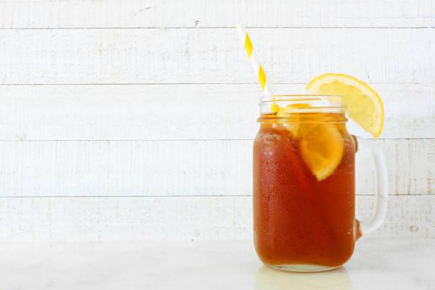 iced tea in a mason jar glass, side view against white wood - comida doce imagens e fotografias de stock