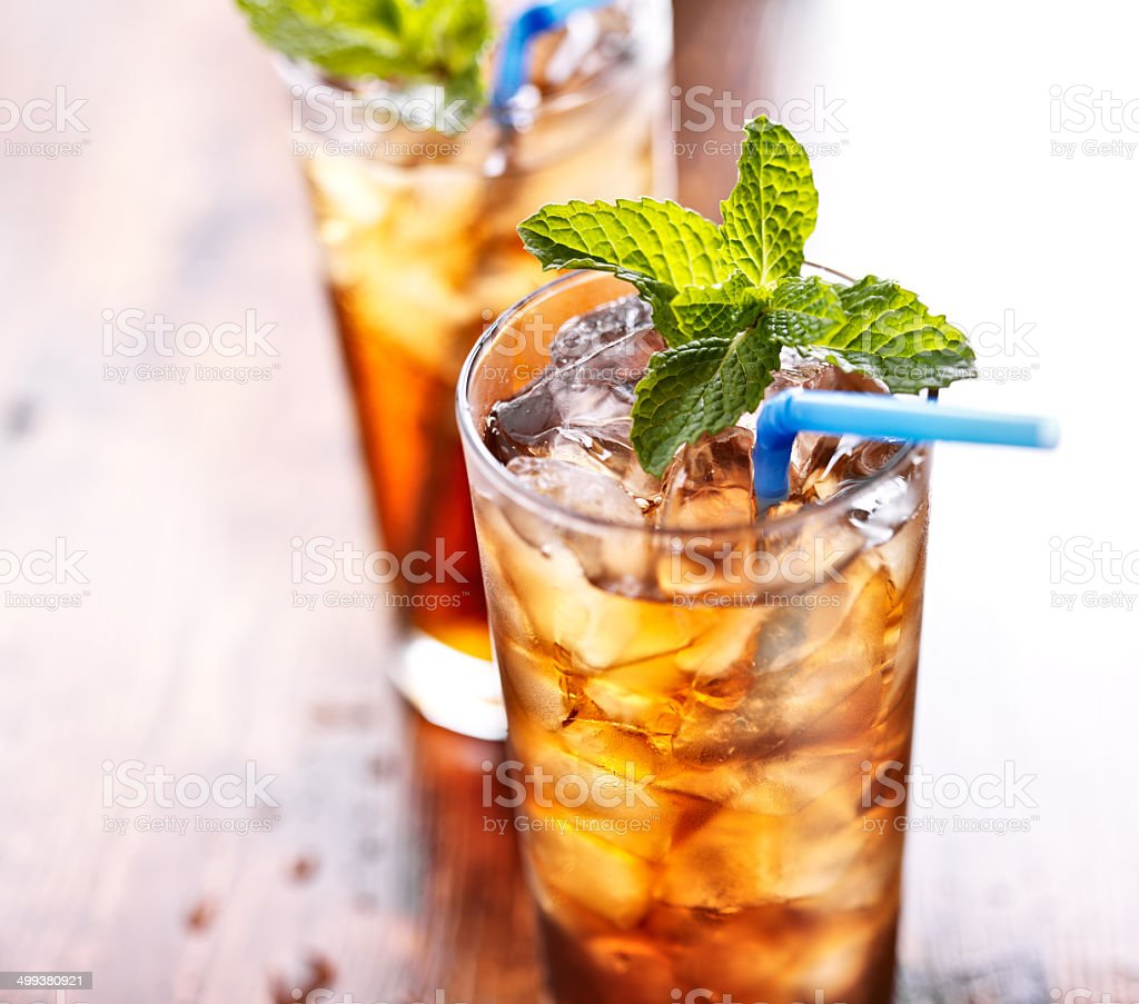 iced tea with blue straw and mint garnish stock photo