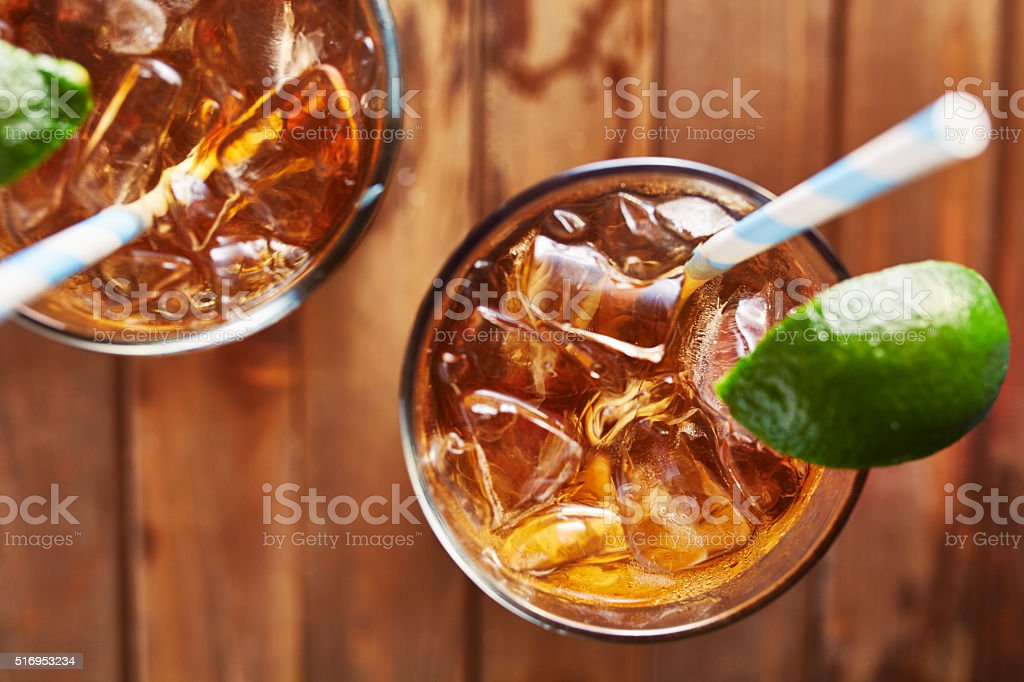 iced tea with lime wedge with retro paper straw stock photo