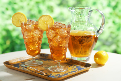 Two glasses of iced tea with pitcher.  Selective focus.