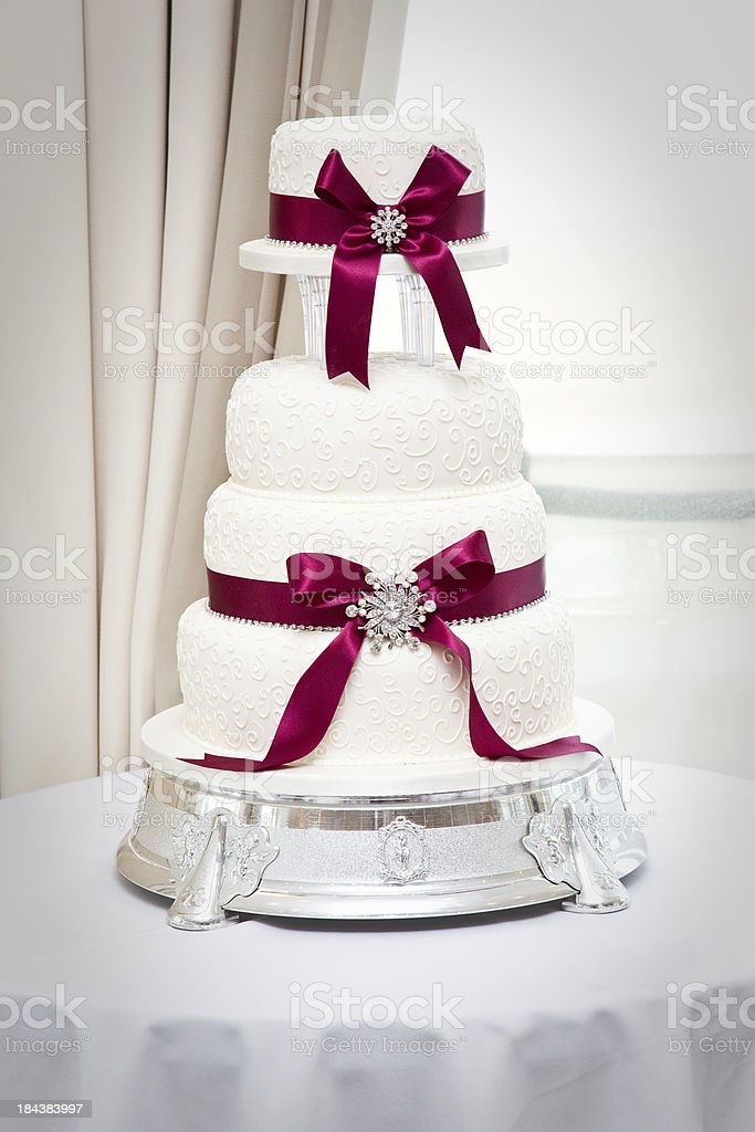 Iced wedding cake with deep red ribbon and jewels stock photo