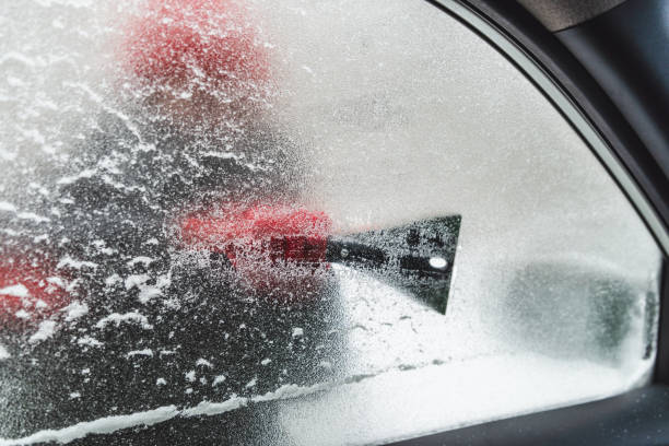 iced window from inside car cleaning snow storm stock photo