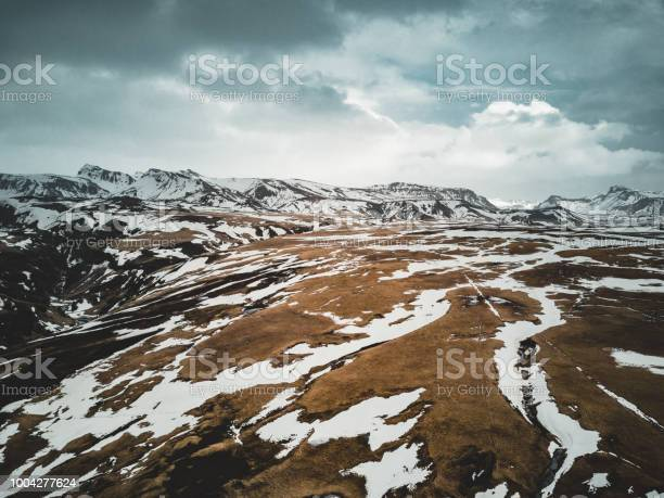 Photo of Iceland aerial view Landscape with snow and clouds, street and yellow and green grass