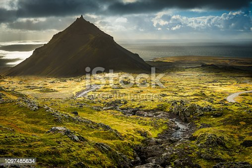 Sunlight beaming through an ocean storm to illuminate the dramatic rugged landscape, volcanic cones and remote Arctic mountains of the Snaefellsnes peninsula in north west Iceland.
