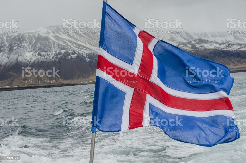 Bandeira da Islândia no barco com montanhas no fundo - foto de acervo