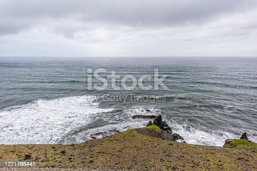 Iceland landscape view from southeast ring road trip brown rocky mountain cliff on cloudy day with Atlantic ocean and waves crashing