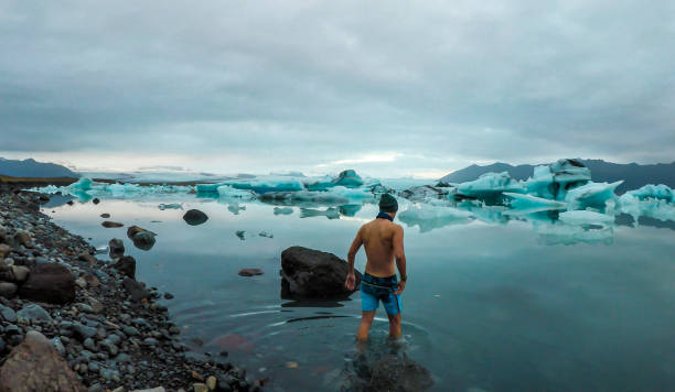 Iceland - Man entering the glacier lagoon Young man enters the icy cold waters of Glacier lagoon. Man wearing only swimming shorts. Ice bergs drifting in the lagoon. Cold temperatures for ice swimming. Calm surface of the water jokulsarlon stock pictures, royalty-free photos & images