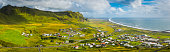 Panoramic view across the rocky valley and green pasture of Vik, the picturesque village nestled beside the ocean in Southern Iceland. ProPhoto RGB profile for maximum color fidelity and gamut.