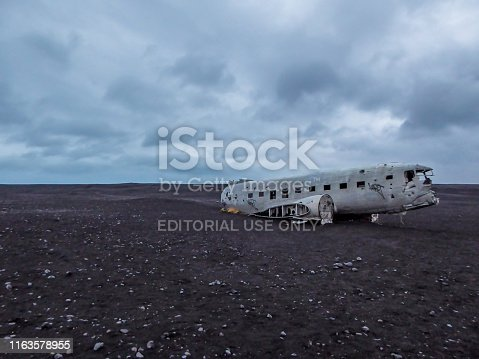 Solheimasandur Plane Wreck located on a black sand beach in Iceland. Few pebbles visible on the black sand. Dark and solemn atmosphere.Plane wreck has no wings and tail anymore.